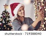 woman hanging christmas lights... | Shutterstock . vector #719388040