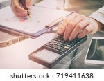 womans hand holding calculator... | Shutterstock . vector #719411638