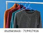 warm woolen sweaters hanging on ... | Shutterstock . vector #719417416