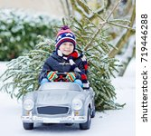 Small photo of Funny little smiling kid boy driving toy car with Christmas tree. Happy child in winter fashion clothes bringing hewed xmas tree from snowy forest. Family, tradition, holiday