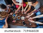 Small photo of Top view creative photo of friends sitting at wooden table. Friends having fun while playing board game.