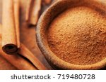 Small photo of Powder cinnamon and sticks and on brown rustic background. Aromatic spices.