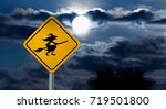 "Dark Cloudy Sky with Full Moon and the road Sign (Yellow Square) ""Caution, Halloween"" is a black Silhouette of the Witch in a Witch Hat Flying on the Broom"
