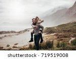young couple piggybacking along ... | Shutterstock . vector #719519008