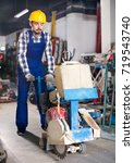 Small photo of Smiling working man practicing his skills with edger at workshop