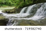 waterfall in a mountain forest | Shutterstock . vector #719582740