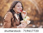 beautiful young woman eating... | Shutterstock . vector #719617720