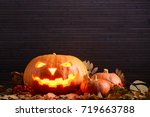Stock photo halloween pumpkin with scary glowing face and two little pumpkins among the yellow leaves 719663788