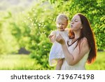 woman and child blowing on a... | Shutterstock . vector #719674198