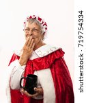 Small photo of Mrs claus is isolated on white and drinking cocoa or coffee and starts laughing