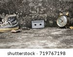 Small photo of Cassette on concrete and old wall as a backdrop. Sneakers and old clock, old story featured a flashback to the 70s-90s.
