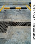 Small photo of Empty car park with black and yellow concrete curb and metal drain cover