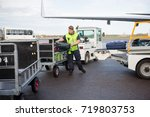 male worker placing luggage in... | Shutterstock . vector #719803753