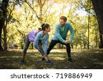 couple stretching in park.... | Shutterstock . vector #719886949
