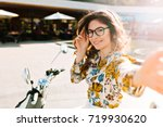 Stock photo cute girl with pretty shy smile making selfie chilling after bike ride around city in weekend 719930620