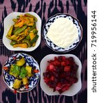 Small photo of Four Uzbek salads on an ikat table cloth
