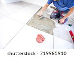 Laying tiles at home. Construction worker laid floor tiles. - stock photo