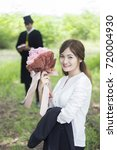 Small photo of Educational theme.Woman graduating getting surprise Beautiful bouquet of congratulations in an academic gown.