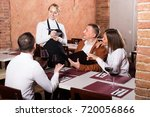 ordinary female waiter writing... | Shutterstock . vector #720056866