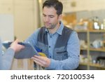 worker signing for delivery | Shutterstock . vector #720100534