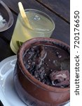 Small photo of Feijoada, traditional bean stew typical of Brazilian cuisine, accompanied by caipirinha, the most famous drink in Brazil, on wooden table