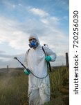 Small photo of Agriculture pest control - Worker in protective workwear in weed control and spraying ambrosia on field.