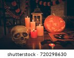 Small photo of Halloween creepy feast decorative hand made frightening stuff on wooden table desk top cutted pumpkin, fall leaves, spider web, net, braincase, lamp. Concept of preparation for evening hallow mas day