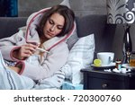 young woman lying ill in bed... | Shutterstock . vector #720300760