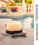 hat and sunglasses by the pool... | Shutterstock . vector #720351478