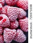 frozen raspberries on dark... | Shutterstock . vector #720371038