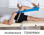 physiotherapist helping patient ... | Shutterstock . vector #720409864
