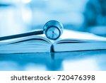 stethoscope on medical book... | Shutterstock . vector #720476398