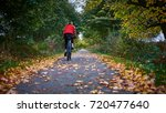 a girl cycles into the distance ... | Shutterstock . vector #720477640
