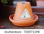 Small photo of Smoking allowed sign in shape of triangle on the ceramic pot on the window sill
