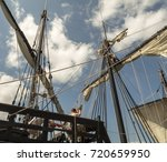 Small photo of Men manually pulling on ropes to furl a sail on an antique tall ship