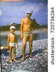 Small photo of USSR, ABKHAZIA, LESELIDZE - CIRCA 1980: Vintage photo of father with little son on beach in Leselidze village, Abkhazia, USSR