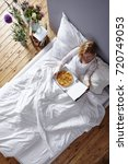 model in white bed eating pizza | Shutterstock . vector #720749053