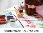 dark haired young woman draws a ... | Shutterstock . vector #720756928