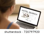 Small photo of Casual woman at home searching hotel on laptop, planning vacation online. Tourist using search engine to find accommodation during trip. Finding best offer for apartment, hotel or motel. Rear view.
