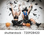 Stock photo two funny young women in leather halloween costumes posing with curved pumpkins over bats and 720928420