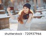 girl walking on snow covered... | Shutterstock . vector #720937966
