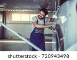 handsome bearded mechanic in... | Shutterstock . vector #720943498
