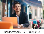 Small photo of Smiling modern entrepreneur working on laptop sitting at table in colorful cafe. Ambitious freelancer, dressed in casual black jacket and unbuttoned shirt typing while thinking about future results.