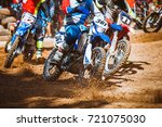 Small photo of Close-up part of mountain bikes race in dirt track with flying debris during an acceleration in sunshine day time. Concept of focus between an accelerate in action sport