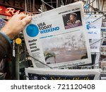 Small photo of PARIS, FRANCE - SEP 23, 2017: Man buying latest newspaper USA TODAY with Hurricane Maria breaking news and picture of damages wind sea water