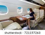 young beautiful woman in Luxury interior in bright colors of genuine leather in the business jet, sky and clouds through the porthole - stock photo