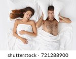 Small photo of Stressed darn haired bearded man blocking ears with pillow, having annoyed expression because of his snoring wife who is sleeping in bed next to him. Snore, insomnia and sleep disorder concept