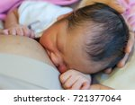 newborn holding mom hand while... | Shutterstock . vector #721377064