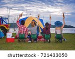Small photo of group of adventure tourist camping cheerful and enjoy together by take up bottle beer in the air, Barbecue camping at the lake in background