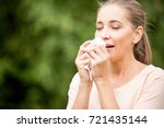 woman with a cold sneezing from ... | Shutterstock . vector #721435144